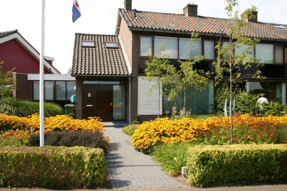 Een schitterende, bloeiende voortuin met siergrassen in Bergschenhoek aan de Rotte. Entree van de woning langs de bloeiende borders begeleid met 3 Amelanciers.