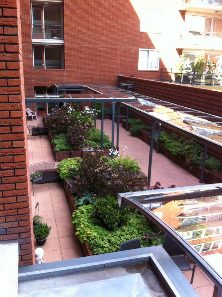 Intensieve daktuin achter een appartementen complex in Naaldwijk