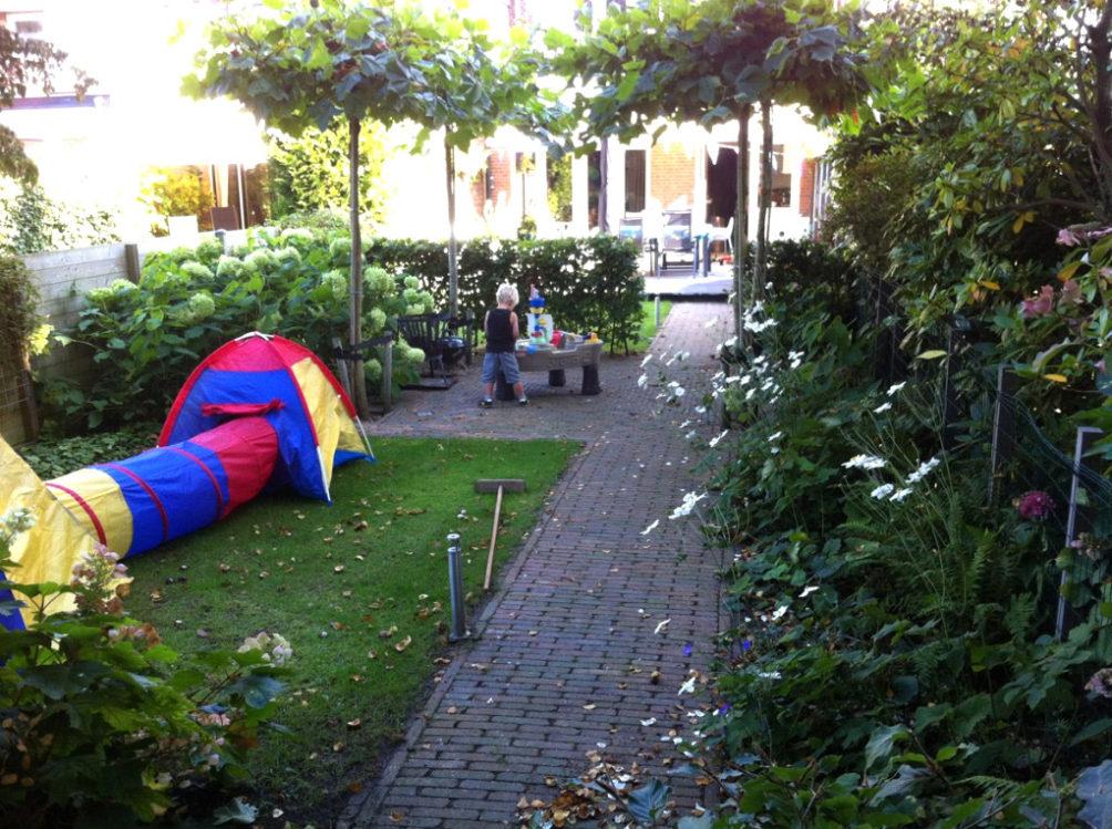 Gezinstuin - Het is heerlijk spelen onder de verkoelende schaduw van de bomen in de tuin in Wassenaar