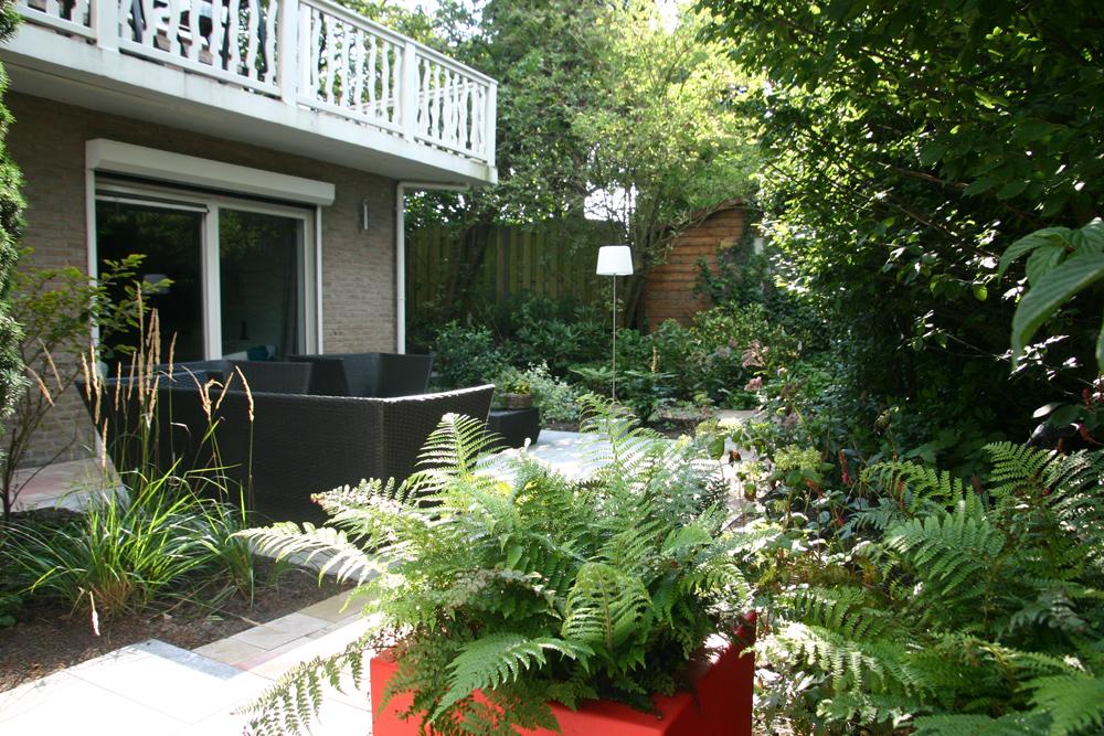Aan de voorkant een compacte tuin langs een doorgaande weg met een greenwall geluidsscherm