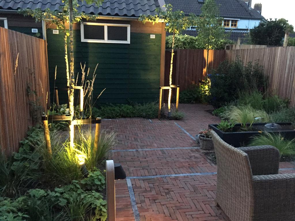 Strakke tuin in Delft met nostalgische bestrating en weelderige beplanting. Het armatuur op de voorgrond is de Beamy Teak van Royal Botania