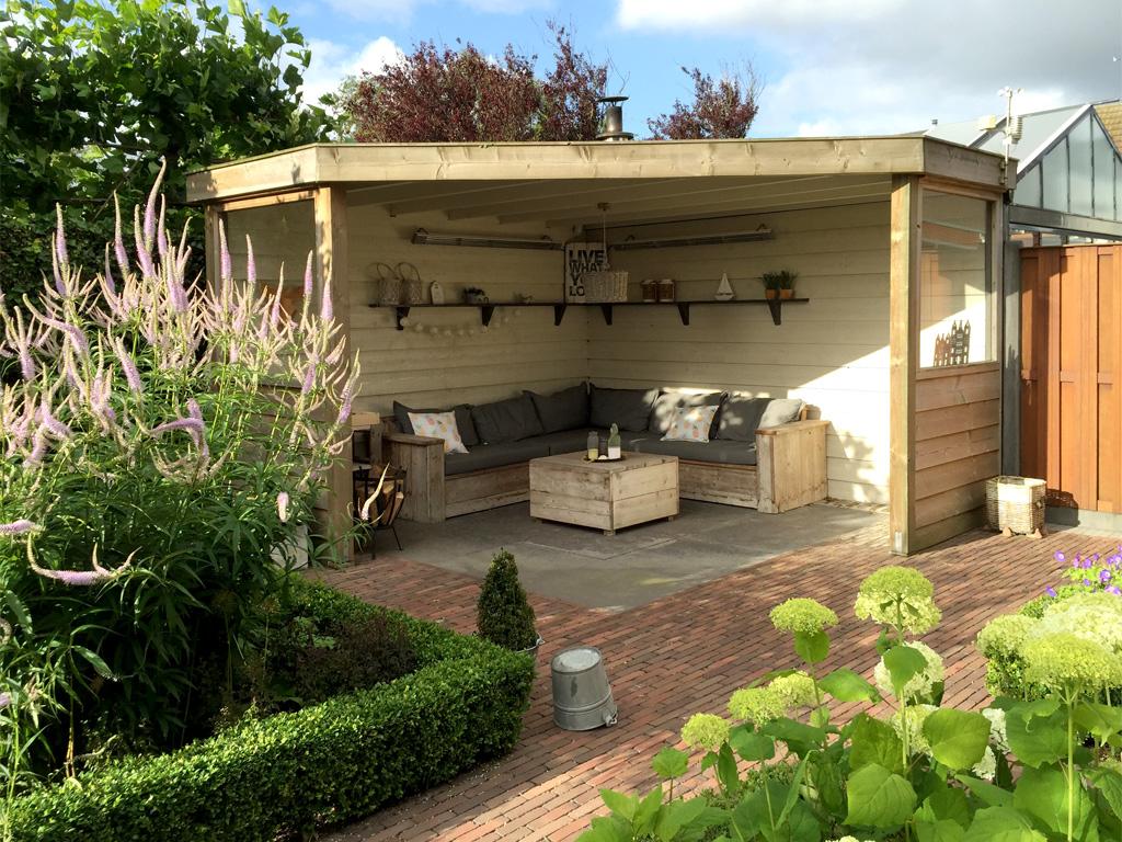 Maatwerk veranda in bloeiende tuin, ingericht met loungebank en terras verwarmers in 's -Gravenzande