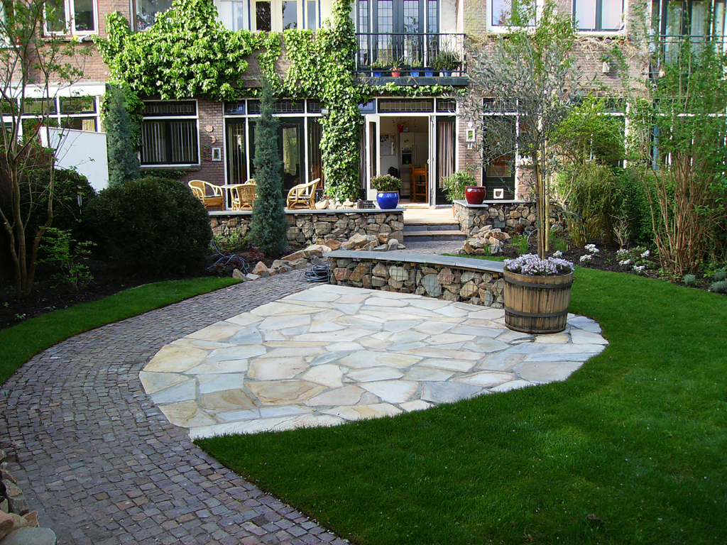 Klassieke tuin in Delft met organische vormen en diverse soorten natuursteen bestrating